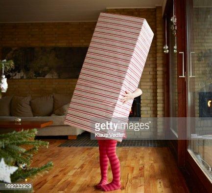 Little girl holding huge present