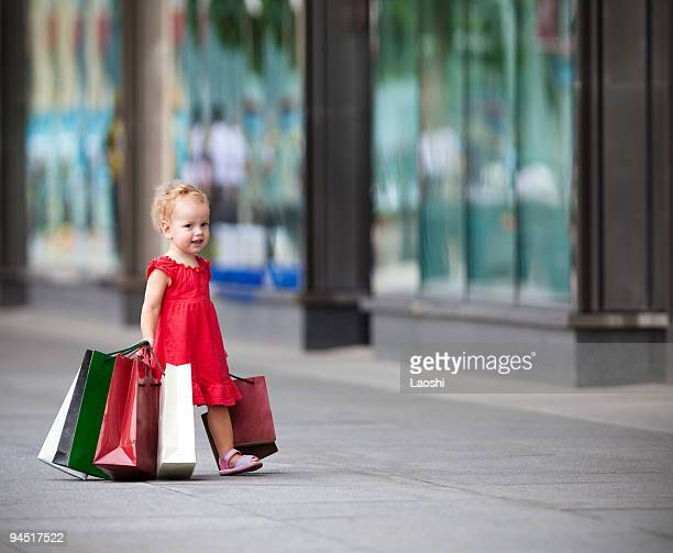 A little girl holding many shopping bags