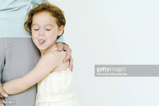 Little girl holding on to mother's leg, sticking tongue out at camera