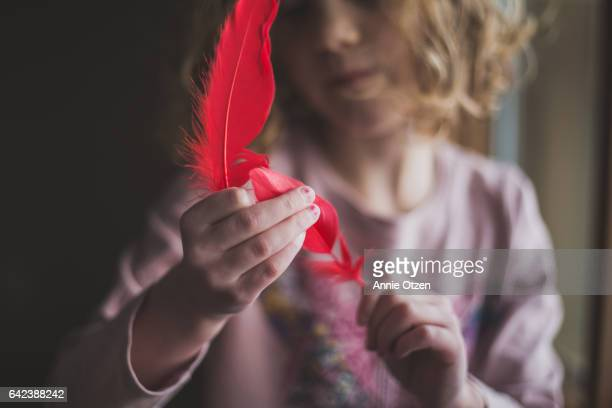 Little Girl Holding Red Feathers