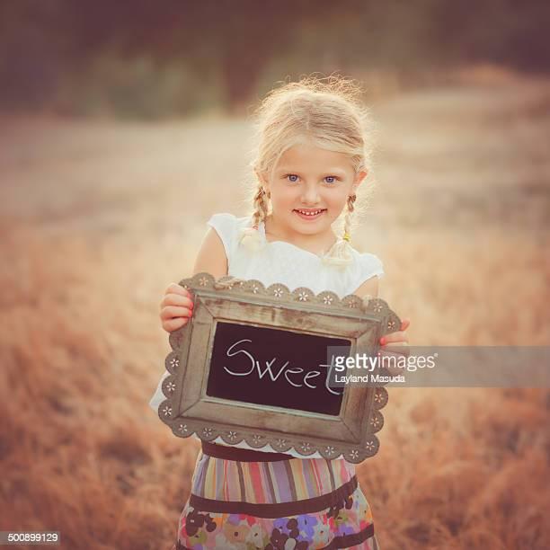 Little Girl Holding The Word Sweet