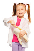 Little girl playing dentist holding tooth model and brush showing proper tooth brushing technique, isolated in white background