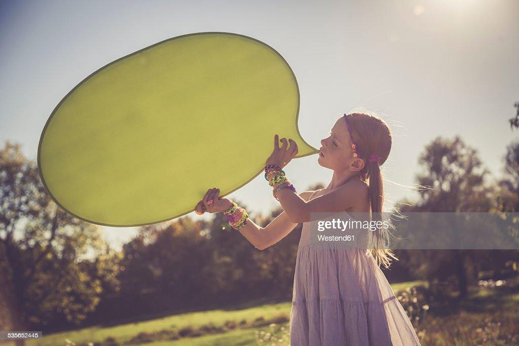 Little girl holding yellow speech balloon