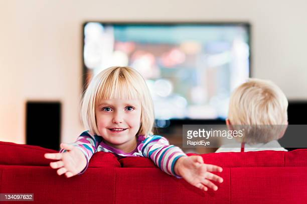 Little girl holds arms out to camera, boy watches TV