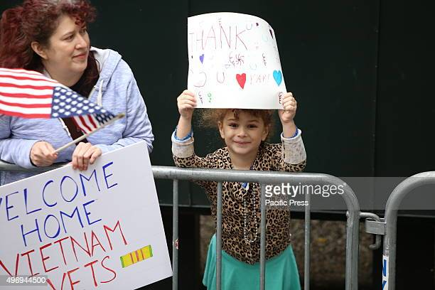 Little girl holds handlettered sign above her head during parade New York City's Veterans Day was led by the US navy as this year's featured service...