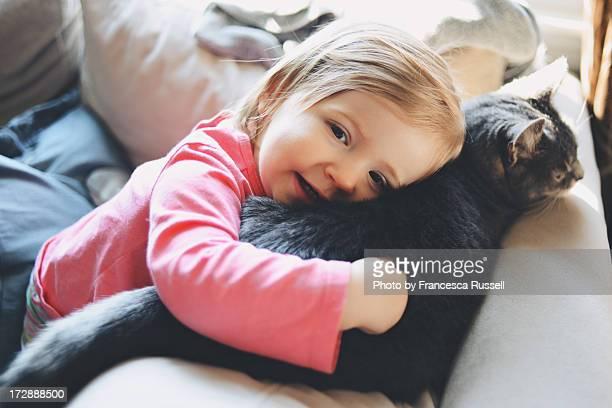 Little girl hugging cat.