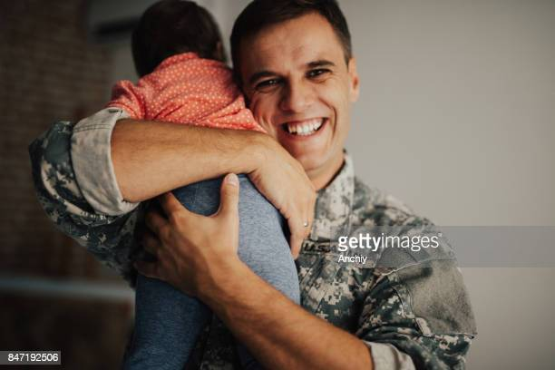 Little girl hugging her military father