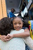 Little Girl Hugging Her Mother Beside the Schoolbus