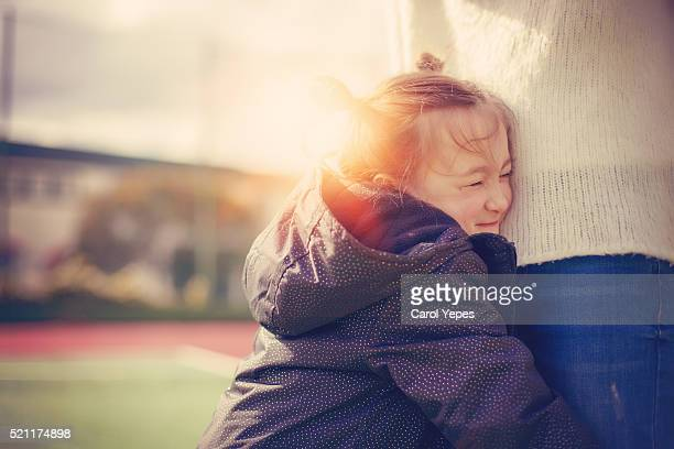 little girl hugging mother´s legs