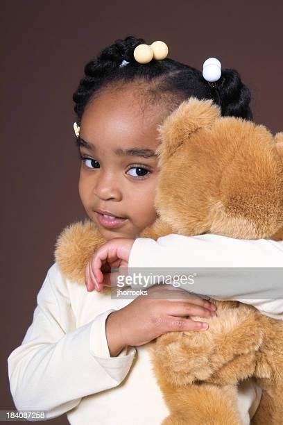 Petite fille embrassant ours en peluche
