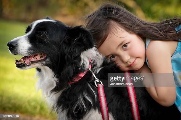 Little girl hugging the back of her dog best friend