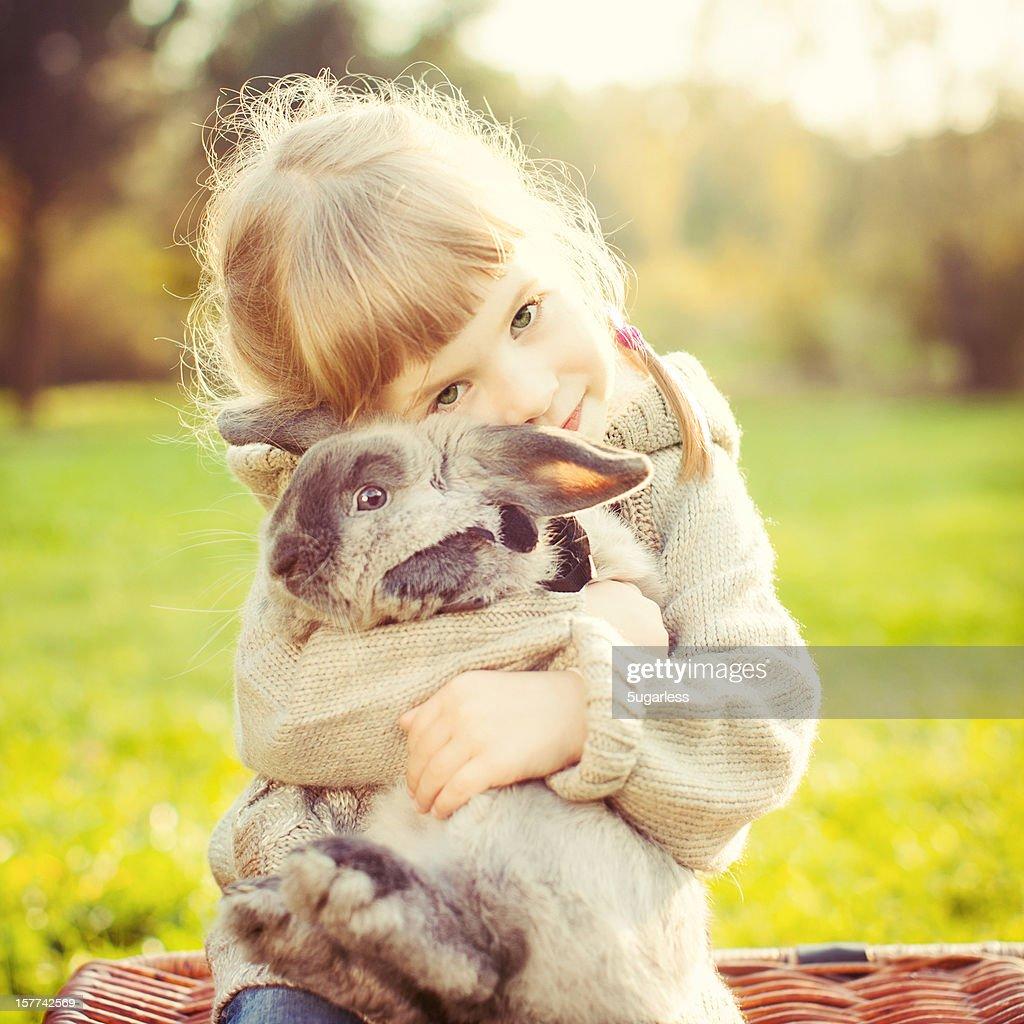 Little girl hugs a rabbit