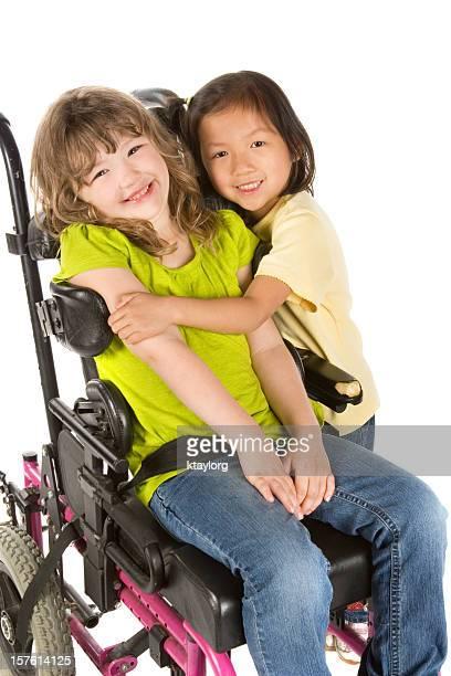 Little girl hugs her friend in wheelchair