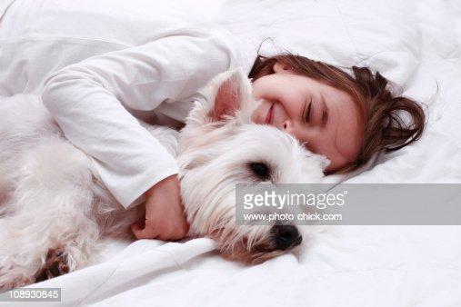 little girl hugs her white dog