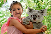 Little girl (age 05) hugs Koala in Queensland, Australia.