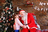 Charming little girl comes to Christmas grandfather who sits on large armchair and whispers in ear most secret desire for New Year cozy spacious room decorated Years holidays with floor lamp, walls wh