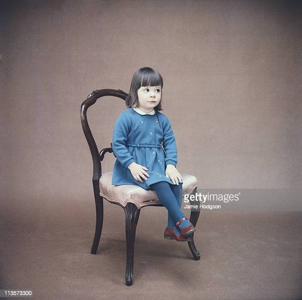 A little girl in a blue dress and tights sits demurely on a chair circa 1970