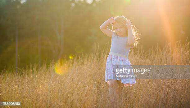Little girl in a field at sunset
