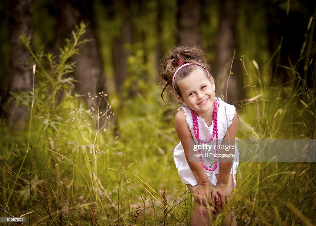 Little girl in a field, smiling at the camera