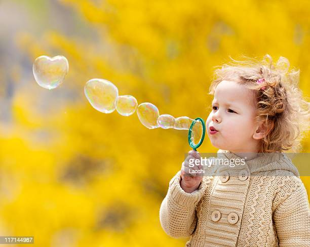 A little girl in a tan sweater blowing bubbles