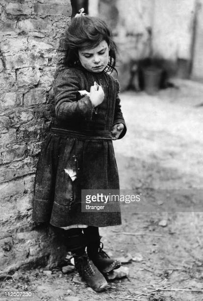 A little girl in a torn dress standing at a street corner probably in Paris France circa 1910