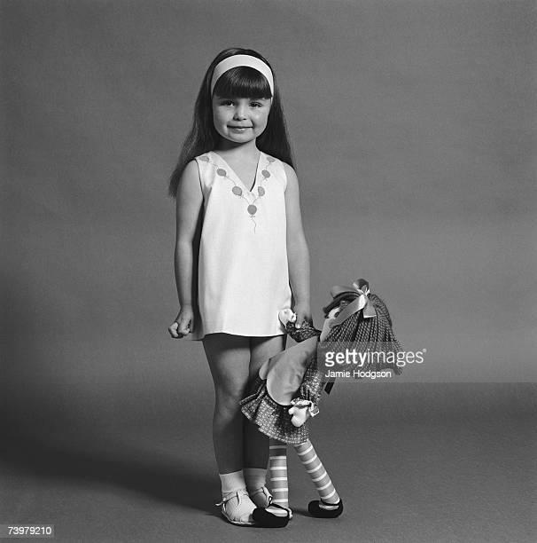 A little girl in a Viyella dress with a rag doll circa 1965