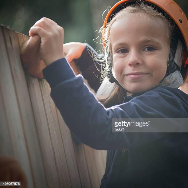Bambina nel parco avventura arrampicata su una parete di legno