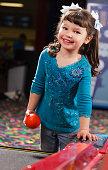 A little girl plays a game in an amusement arcade.