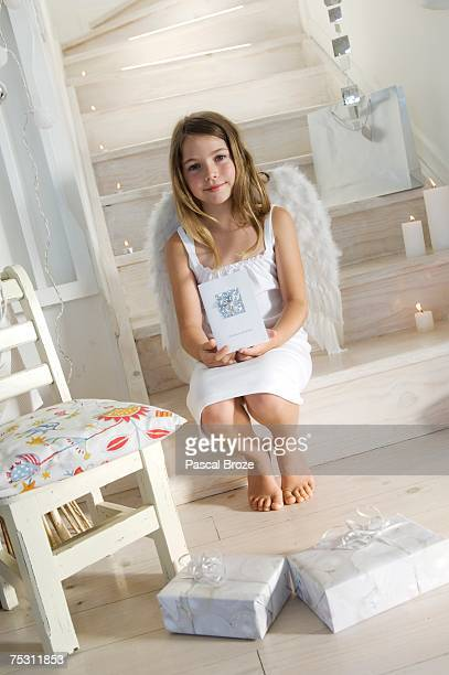 Little girl in an angel costume, holding a Christmas card, indoors