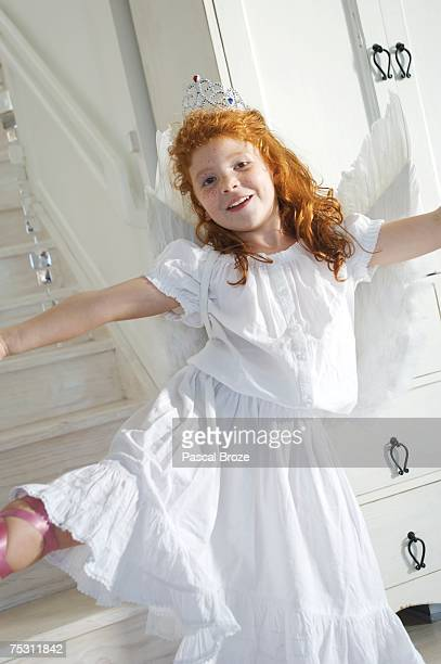 Little girl in an angel costume, looking at the camera, indoors