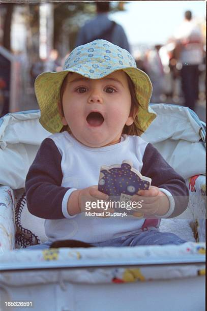 Little girl in baby carriage and a baby book Aleksa Martinol yr with mom Virlananot in photos Toronto res Women at Harlequin boothspno names There...