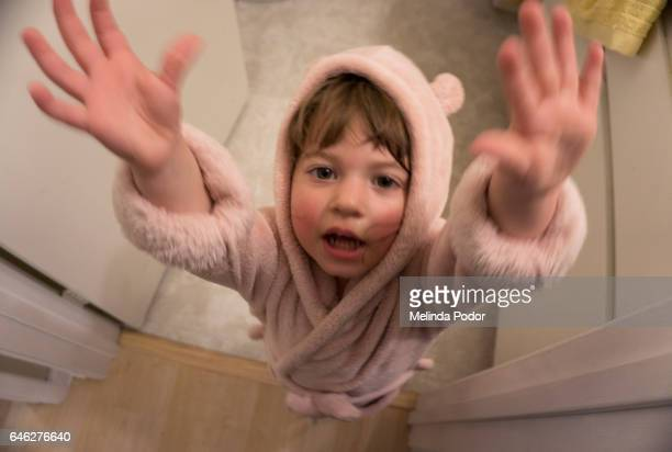 Little girl in bathrobe wanting to be picked up