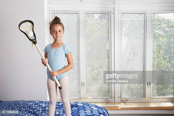 Little girl in bedroom holding racket and ball