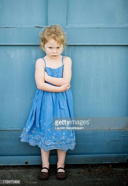 Little girl in blue dress against blue wall