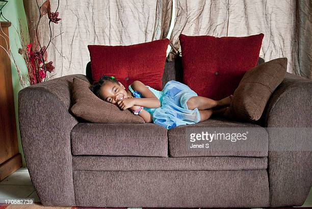 Little girl in blue dress lying on a couch.