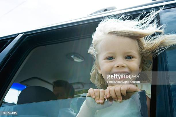 'Little girl in car, looking out of window, smiling at camera, hair blowing in wind'