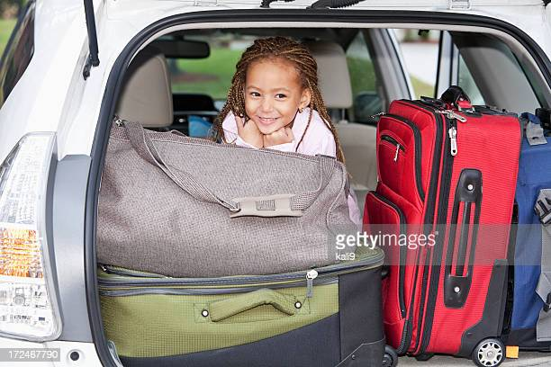 Little girl in car packed for trip