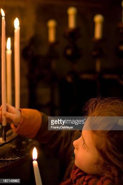 Kleines Mädchen in der Kirche, Beleuchtung eine Kerze