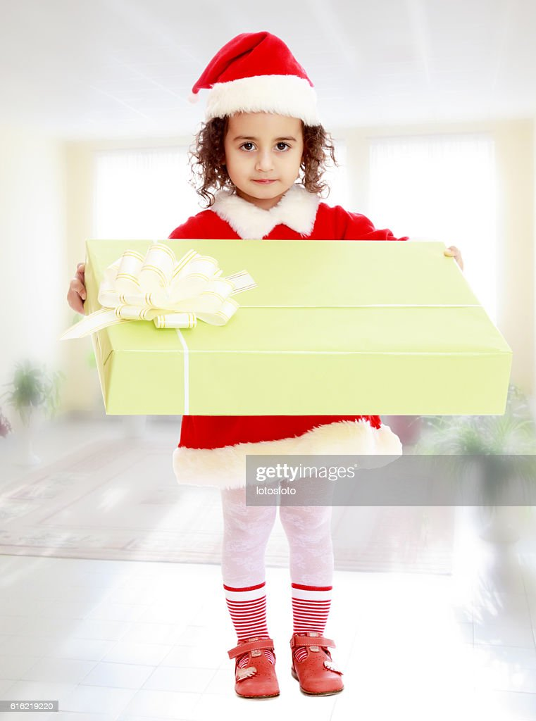 Little girl in costume of Santa Claus with gift : Photo