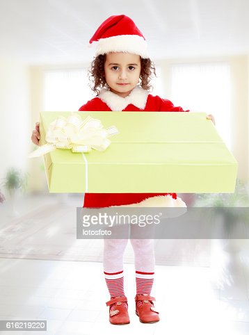 Little girl in costume of Santa Claus with gift : Stock Photo