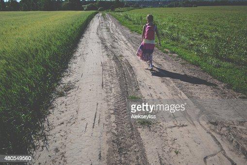 Little girl in dress walking along the road : Stock Photo