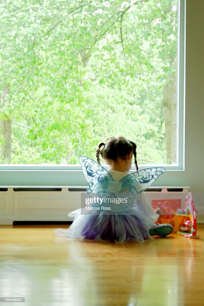 Little girl in fairy costume playing by window : Stock Photo