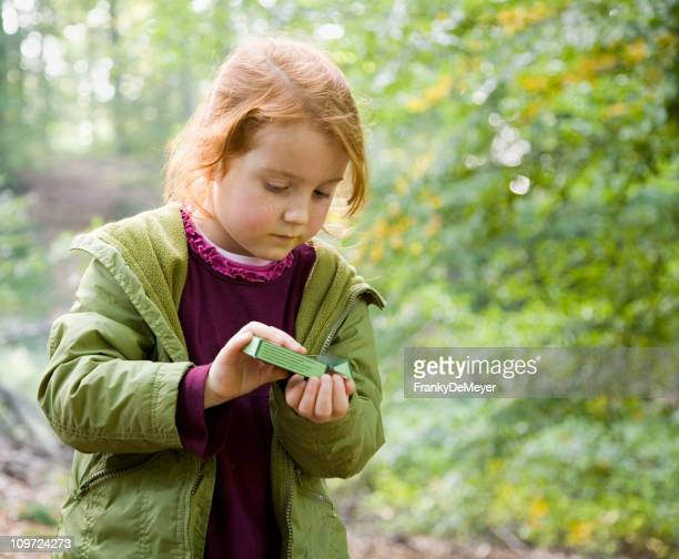 Little Girl in Forest Taking Candy from Box