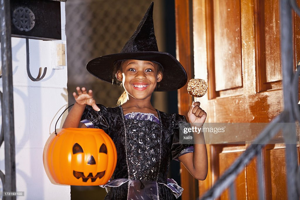 little girl in halloween costume with candy apple stock photo - Apple Halloween Costumes