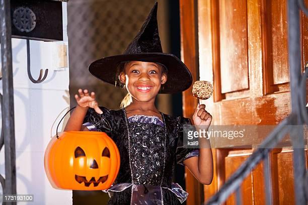 Menina na Fantasia de Dia das Bruxas com Maçã Doce