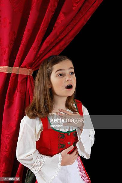 A little girl in her costume in Dirndl singing