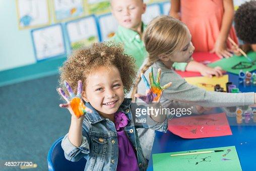 Little girl in kindergarten class doing art project