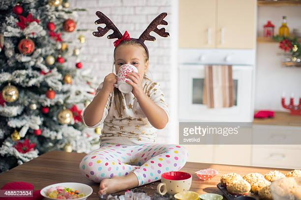 Little girl in kitchen for christmas eating muffins.
