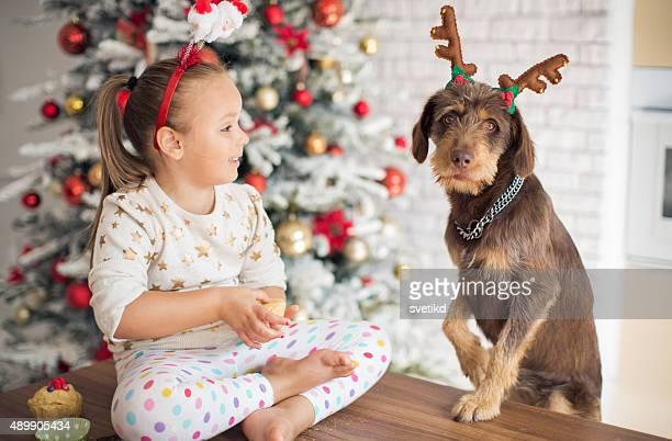 Petite fille dans la cuisine pour Noël avec son chien.