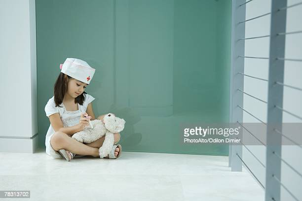 Little girl in nurse hat giving teddy bear shot